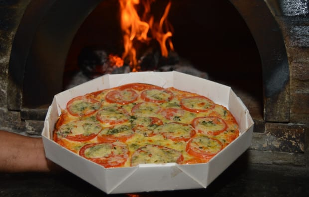 Foto da melhor pizza de salvador, a Pizza de Gorgonzola assada no forno à lenha na caixa do delivery